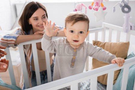 Photo pour Bébé garçon agitant les mains près heureux tatoué mère sur fond flou - image libre de droit