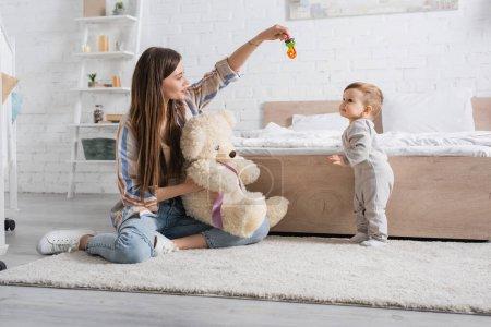 Photo pour Étonnante jeune mère tenant ours en peluche et hochet près du fils de l'enfant - image libre de droit
