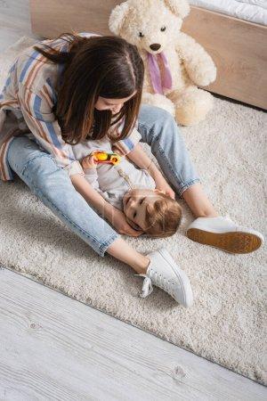aus der Vogelperspektive: Tätowierte junge Mutter spielt mit Säugling, der Rassel hält