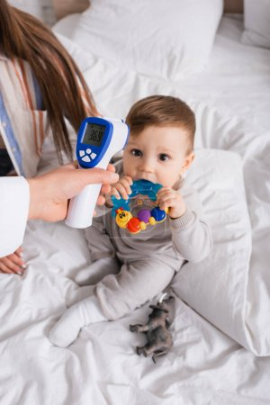 Photo pour Pédiatre examinant le nourrisson garçon avec thermomètre sans contact près de la mère - image libre de droit