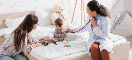 heureux pédiatre afro-américain en manteau blanc assis sur le lit et examinant bébé garçon avec stéthoscope, bannière