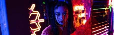 stylische junge asiatische Frau schaut in die Kamera in der Nähe Neon-Beleuchtung außerhalb, Banner