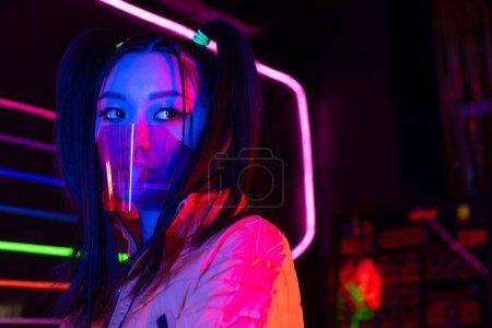 junge Asiatin mit Gesichtsschutz in der Nähe von Neonlicht