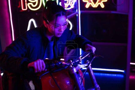 Photo pour Stylish young asian woman in sunglasses riding motorcycle - image libre de droit
