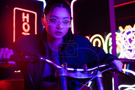 young asian woman in sunglasses riding motorcycle with neon lighting behind