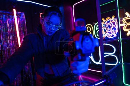 Photo pour Armed asian woman in sunglasses aiming with gun while riding motorcycle near neon sign - image libre de droit