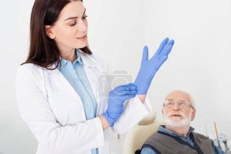 dentiste en manteau blanc ajustant des gants en latex près d'un patient âgé assis dans une chaise dentaire