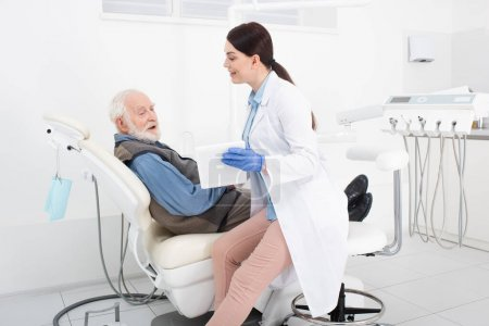smiling dentist showing tablet to elderly patient in dental clinic