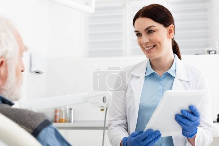 cheerful dentist with tablet in hands looking at senior patient sitting in dental chair