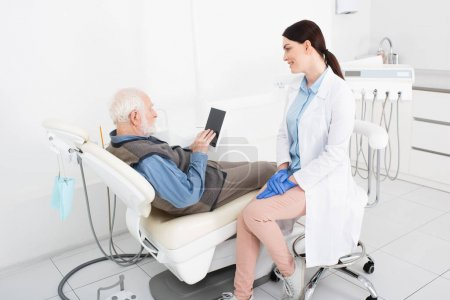 Photo for Senior man lying in dental chair and looking at tablet near doctor in dental clinic - Royalty Free Image