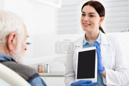 cheerful dentist showing tablet to senior patient in dental clinic