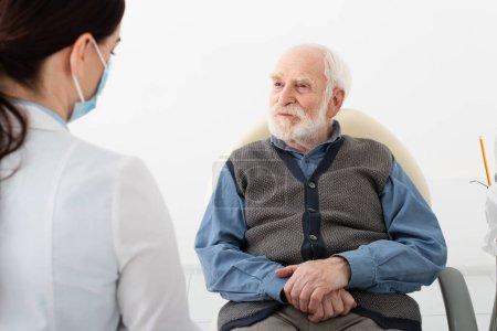 Photo pour Patient âgé en chaise dentaire en consultation avec un médecin en masque médical - image libre de droit