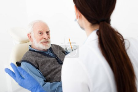 Photo for Senior patient in dental chair taking consultation from doctor in clinic - Royalty Free Image