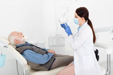 dentist in medical mask and blue latex gloves touching medical lamp in front of senior patient in dental chair