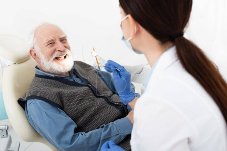 smiling senior man having teeth treatment by dentist in latex gloves in dental clinic