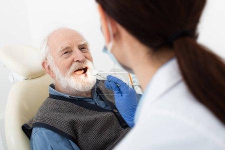senior man having teeth examination by dentist in latex gloves with mirror in hand in dental chair
