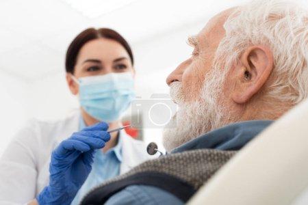 Photo pour Dentiste en masque médical examinant les dents de l'homme âgé avec sonde et miroir dans la chaise dentaire - image libre de droit