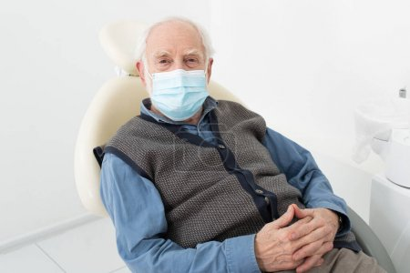 senior man in medical mask sitting in dental chair in clinic