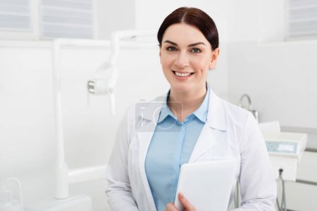 portrait of smiling dentist holding tablet and looking at camera in dental clinic