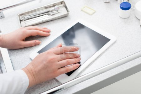 Photo for Partial crop view of female hands typing on tablet with blank screen near dental equipment on medical table - Royalty Free Image