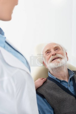 smiling senior patient lying in dental chair with dentist hand on shoulder