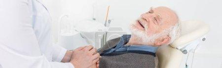 grateful elderly patient in dental chair holding hands with dentist, banner