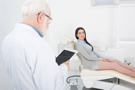 senior dentist looking at blank screen tablet in front of blurred patient in dental chair in clinic