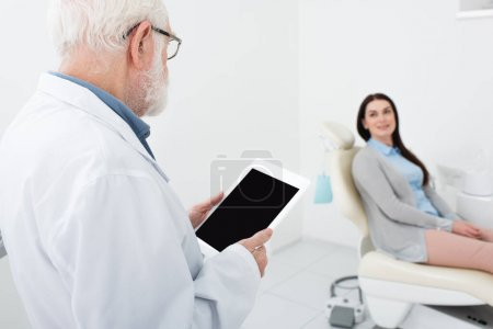 senior dentist standing with tablet in front of patient in dental clinic