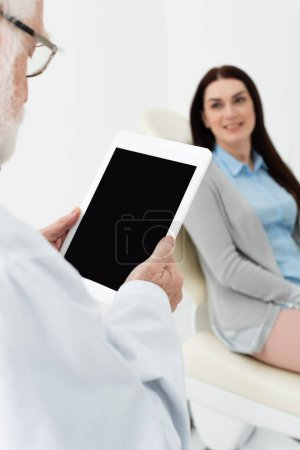 Photo for Senior dentist standing with blank screen tablet in front of blurred woman in dental chair in clinic - Royalty Free Image
