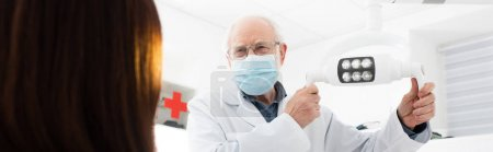 senior dentist in medical mask touching medical lamp in front of patient, banner