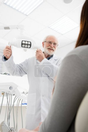 cheerful senior dentist touching medical lamp in front of woman in dental chair