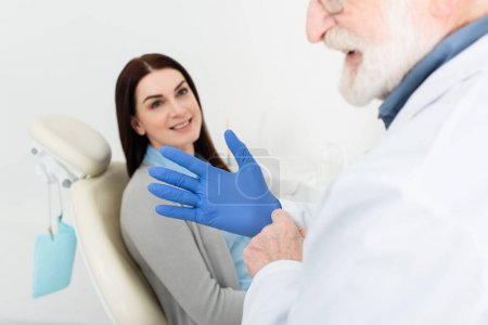 dentist adjusting latex gloves before examination of patient sitting in dental chair