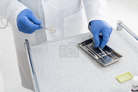 cropped view of doctor in latex gloves taking dental metal equipment from tray in clinic