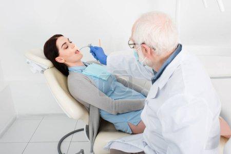 Photo pour Dentiste chevronné faisant le traitement des dents du patient en fauteuil dentaire - image libre de droit