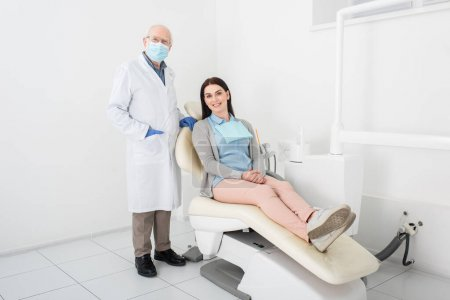 senior dentist in medical mask and latex gloves standing near pretty woman sitting in dental chair in clinic