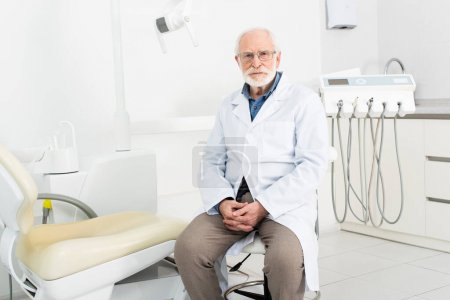 Zahnarzt im weißen Kittel sitzt mit geballten Händen in Zahnklinik