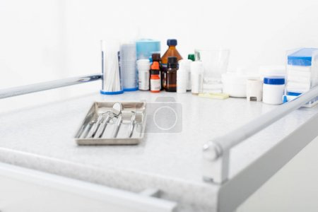 Photo for Medicines and clean dental metal tools in tray on medical table - Royalty Free Image