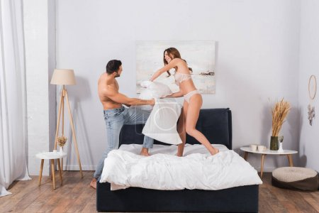 Smiling woman in lingerie pillow fighting with boyfriend in jeans