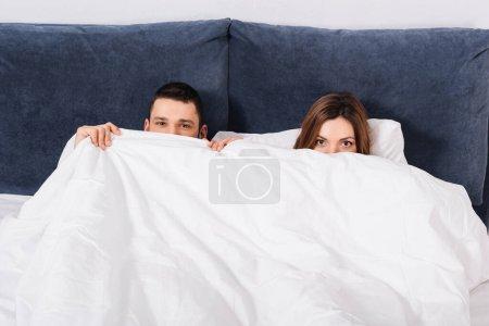 Photo pour Couple regardant la caméra tout en couvrant les visages avec une couverture - image libre de droit