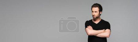 Photo pour Homme barbu en t-shirt noir posant avec les bras croisés isolés sur gris, bannière - image libre de droit