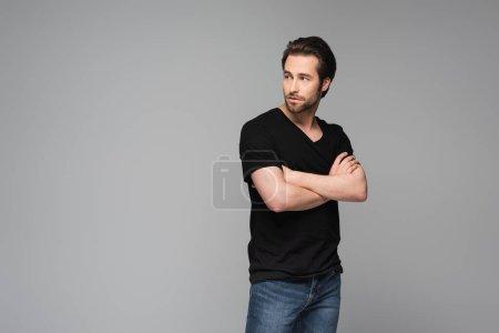 Photo pour Jeune homme barbu en t-shirt noir posant avec les bras croisés isolés sur gris - image libre de droit