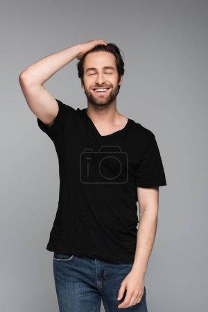 hombre barbudo alegre con los ojos cerrados posando aislado en gris