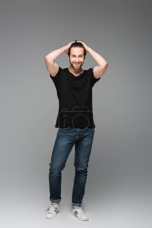 Photo for Full length of bearded man in jeans and black t-shirt posing and smiling on grey - Royalty Free Image