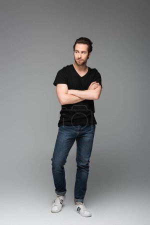 Photo for Full length of bearded man in jeans and black t-shirt posing with crossed arms on grey - Royalty Free Image