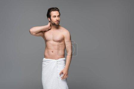 hombre sin camisa envuelto en toalla de pie aislado en gris