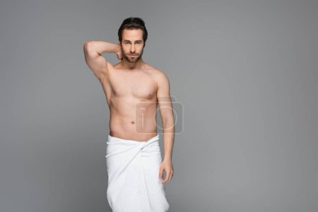 muscular man wrapped in white towel posing isolated on grey