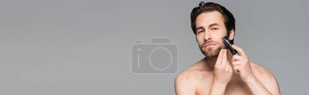 homme torse nu utilisant rasoir électrique isolé sur gris, bannière