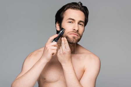 Photo for Shirtless man with beard using electric razor isolated on grey - Royalty Free Image