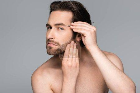 bearded and shirtless man tweezing eyebrow isolated on grey