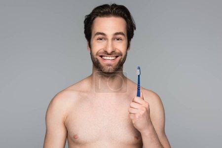 Photo pour Homme joyeux et torse nu tenant la brosse à dents isolée sur gris - image libre de droit